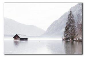 Allmsee met botenhuis in de regen en mist